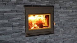 A small focus 250 fireplace is positioned in the centre of the image, surrounded with thin cultured stone facing material, the fire can be observed burning through the fireplace glass doors.