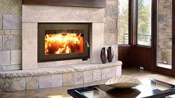 Focus 320 wood-burning fireplace is burning wood, large glass fireplace door above the fireplace opening is a custom fireplace mantel.