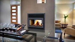 Focus ST Double Sided Wood Burning Fireplace, the image displays a fire burning through the fireplace glass door.