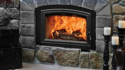 Opel 3 wood burning fireplace with natural grey stone, fire can been seen burning through the large fireplace glass door