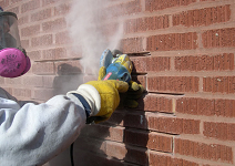 Chimney Technician using a grinder to remove mortar between chimney bricks